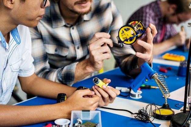 Gruppe von personen, die an der elektronischen reparaturwerkstatt arbeitet