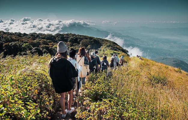Gruppe von personen, die auf berg im morgensonnenaufgang, trekking geht.