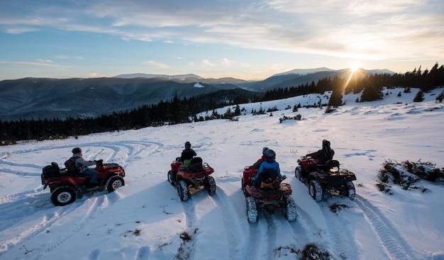 Gruppe von personen, die auf viererkabelfahrrädern nicht für den straßenverkehr, schönen sonnenuntergang in den bergen im winter genießend sitzt