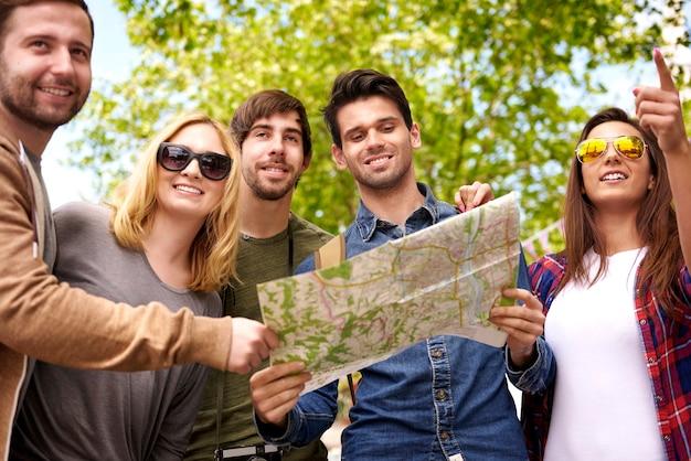 Gruppe von personen, die eine karte verwenden, um ein ziel zu suchen