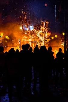 Gruppe von personen, die erwägt, wie ein pappmonument in valencianischen fallas brennt.