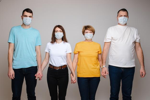 Gruppe von personen, die hände halten, die in der medizinischen sicherheitsmaske aufwerfen