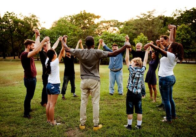 Gruppe von personen, die hand im park zusammenhält