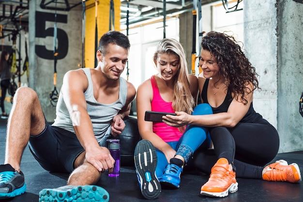 Gruppe von personen, die handy im fitness-club betrachtet