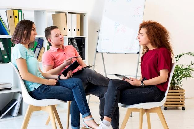Gruppe von personen, die im studienraum beim halten der digitalen tablette und des klemmbrettes sich bespricht