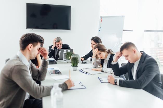 Gruppe von personen, die in einem konferenzzimmer schlafend sich fühlt, nachdem zu viel gearbeitet worden ist.