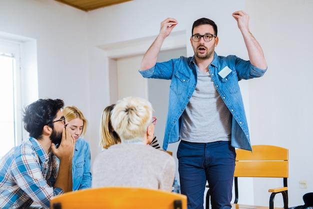 Gruppe von personen, die in einem kreis auf gruppentherapie sitzen. ein mann steht und spricht über seine erfahrungen.