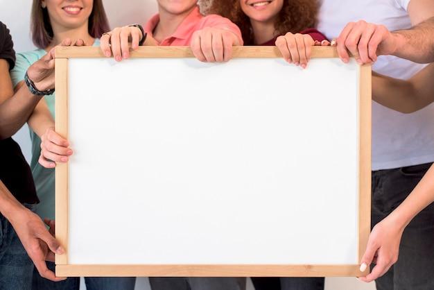 Gruppe von personen, die leeren weißen bilderrahmen mit hölzernem internatsschüler hält