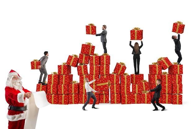 Gruppe von personen, die mit dem weihnachtsmann zusammenarbeiten, um geschenkpakete vorzubereiten