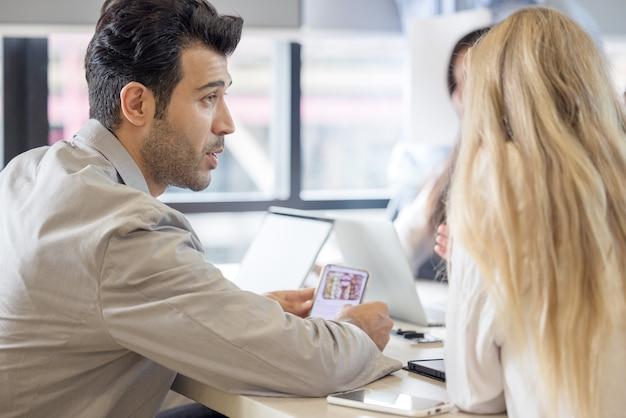 Gruppe von personen, die mobiltelefon verwenden und betrachten, geschäftsprojektteam, das im besprechungsraum im büro zusammenarbeitet