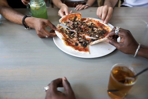 Gruppe von personen, die nahes hohes der pizza isst
