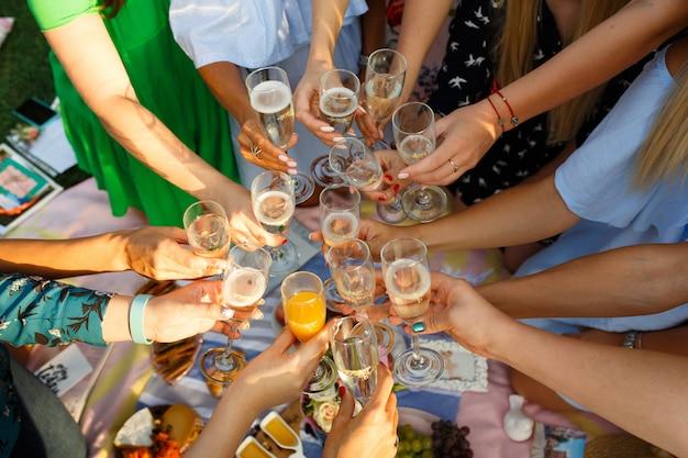 Gruppe von personen, die picknickmahlzeitzusammengehörigkeit im freien hat, die gläser röstend speist