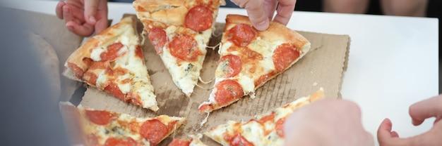 Gruppe von personen, die pizzascheiben in nahaufnahme nimmt