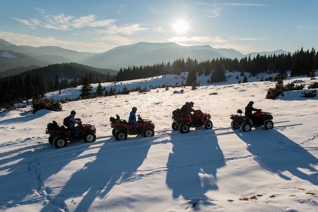 Gruppe von personen, die sonnenuntergang auf viererkabelfahrrädern auf schnee in den bergen im winter genießt
