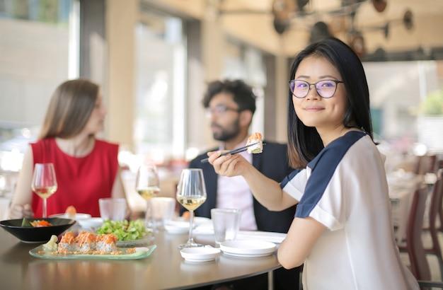Gruppe von personen, die sushi in einem restaurant isst
