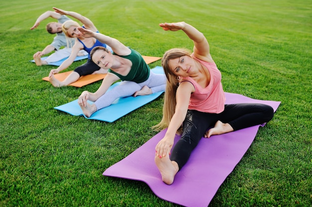 Gruppe von personen, die yoga auf dem grünen feld tut