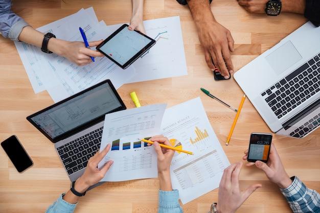 Gruppe von personen, die zusammen mit laptops, tablets und smartphones arbeiten und einen finanzbericht erstellen