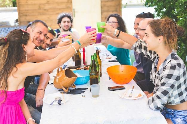 Gruppe von personen, die zusammen zu mittag essen und rösten sitzt