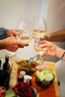 Gruppe von personen, erwachsene in der nacht zu hause oder restaurant, die etwas feiern, zum beispiel einen geburtstag oder einen anderen erfolg mit einem glas mit weinrebe