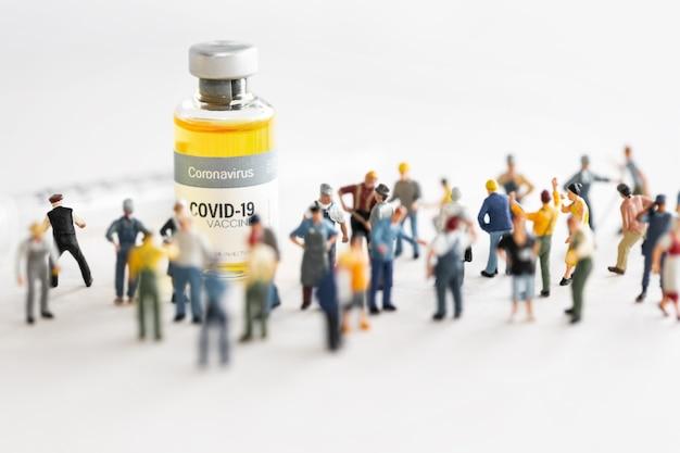 Gruppe von personen (figur), die gegen den coronavirus covid-impfstoff und die spritze zur injektion stehen