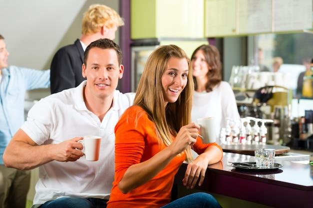 Gruppe von personen in trinkendem kaffee des cafés