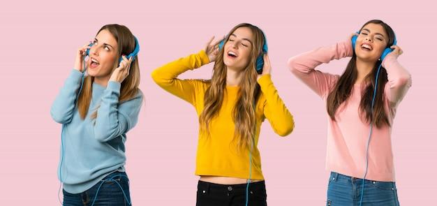 Gruppe von personen mit bunter kleidung hörend musik mit kopfhörern auf buntem backg