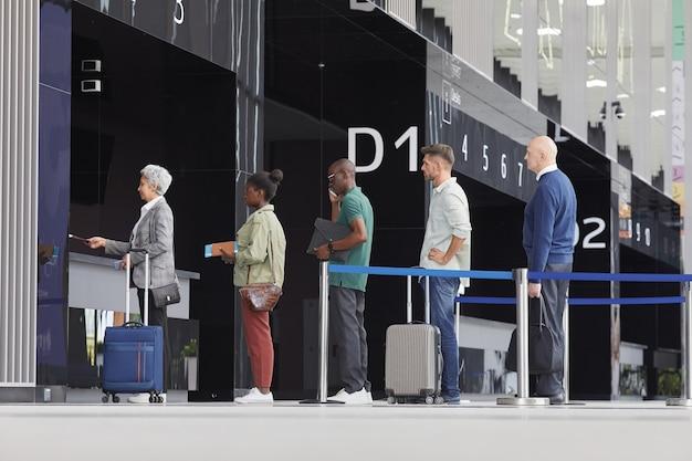 Gruppe von personen mit gepäck, die in einer schlange nahe dem abfluggate am flughafen stehen