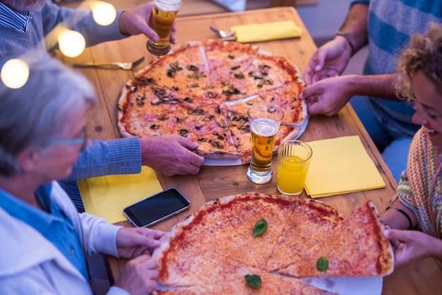 Gruppe von personen oder familie am holztisch, die zusammen mit zwei großen pizzen pizza isst - zwei senioren und zwei frauen, die zusammen etwas oder eine party feiern?