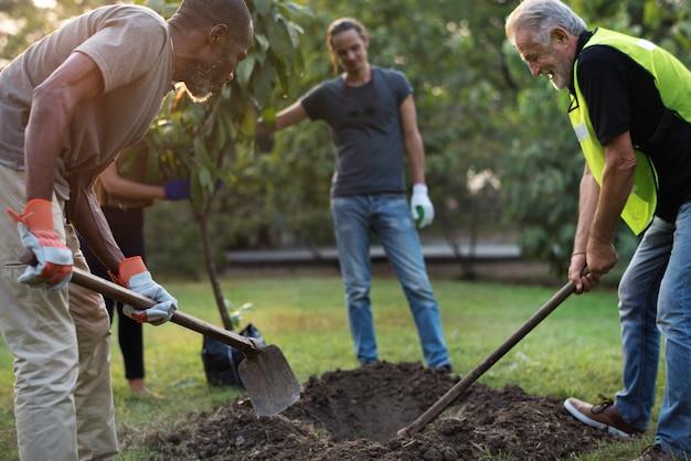 Gruppe von personen pflanzen einen baum zusammen im freien