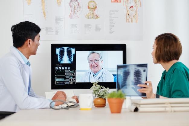 Gruppe von pneumologen aus aisan, die über röntgenaufnahmen des brustkorbs und neue wege der behandlung von lungenentzündungen diskutieren