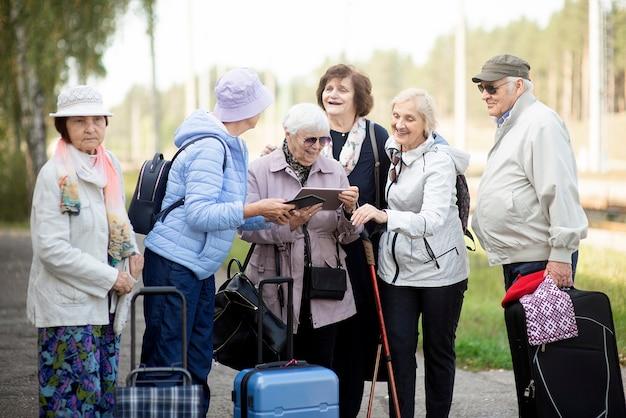 Gruppe von positiven älteren älteren leuten, die digitale karte auf reisen betrachten.