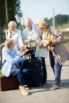 Gruppe von positiven älteren leuten, die karte auf reisen betrachten.
