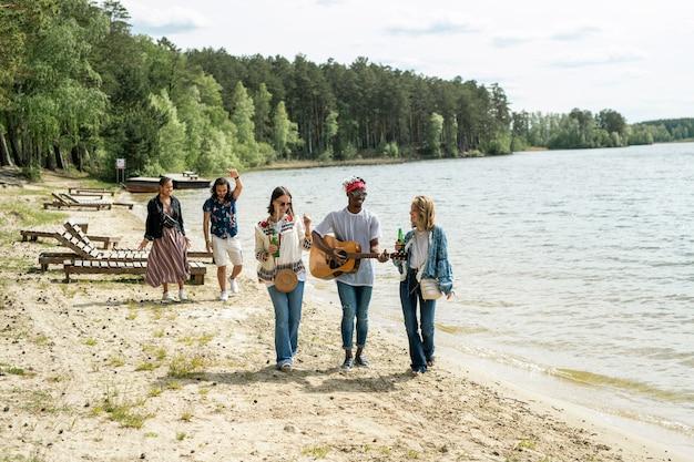 Gruppe von positiven jungen multiethnischen freunden, die strandspaziergang genießen, während schwarzer kerl gitarre in bewegung spielt
