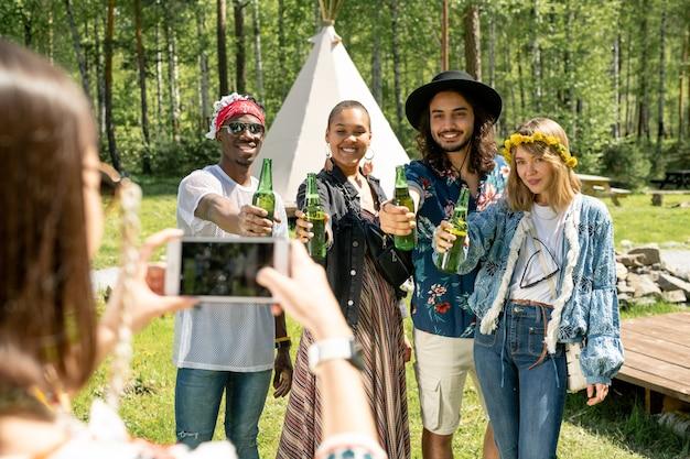 Gruppe von positiven jungen multiethnischen leuten in hippie-outfits, die mit bierflaschen für foto beim landschaftsfest aufwerfen