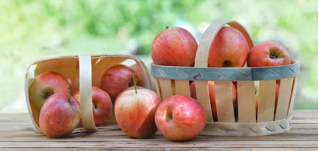 Gruppe von roten äpfeln in körbchen auf einem holztisch