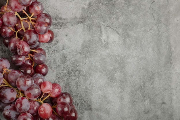 Gruppe von roten frischen reifen trauben auf marmoroberfläche.