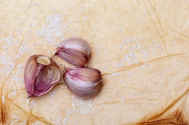 Gruppe von roten knoblauchzehen und salzkörnern. auf einem schönen rustikalen vanillehintergrund. platz zum einfügen ihres textes (text kopieren)