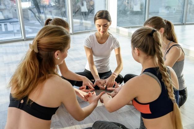 Gruppe von schönen frauen, die yoga im fitnessstudio praktizieren