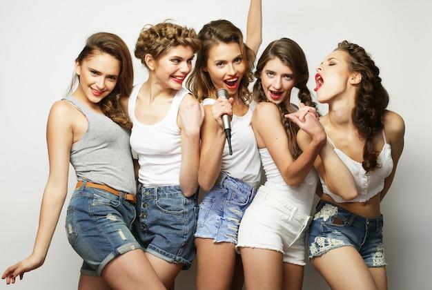Gruppe von schönen stilvollen hipster-mädchen, die karaoke singen