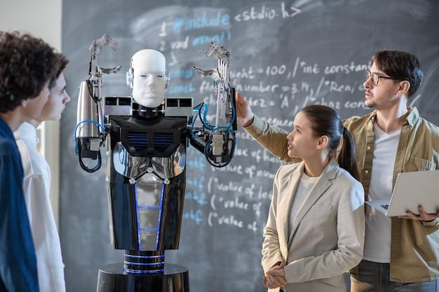 Gruppe von schülern, die computersteuerungsroboter mit erhobenen händen betrachten, während ihr lehrer seine fähigkeiten im unterricht demonstriert