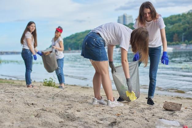 Gruppe von schülern mit lehrer in der natur, die plastikmüll reinigen. umweltschutz, jugend, freiwilligenarbeit, wohltätigkeit und ökologiekonzept
