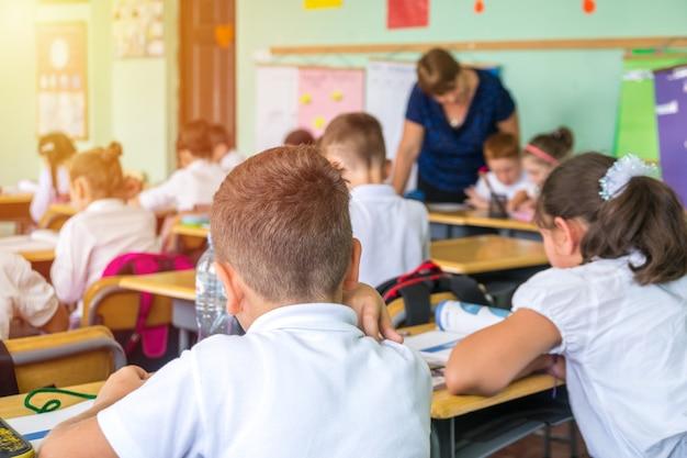 Gruppe von schulkindern, die sitzen und lehrer im klassenzimmer von hinten hören.