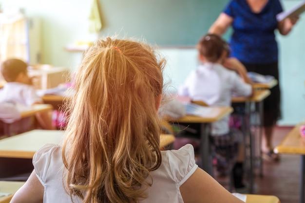 Gruppe von schulkindern, die sitzen und lehrer im klassenzimmer von hinten hören