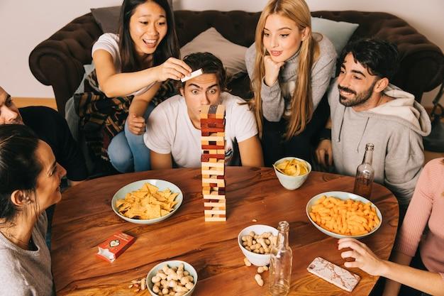 Gruppe von sechs glücklichen freunden, die tabletopspiel spielen
