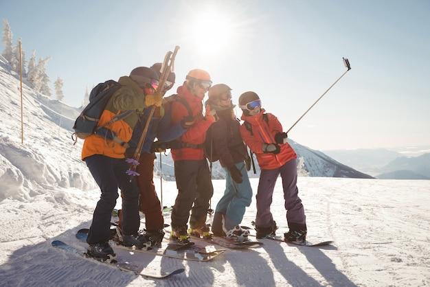 Gruppe von skifahrern, die selfie auf handy nehmen
