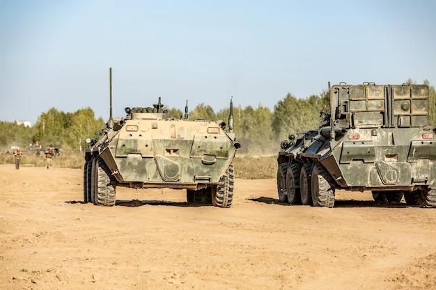 Gruppe von soldaten auf panzern im freien bei armeeübungen. kriegs-, armee-, technologie- und menschenkonzept