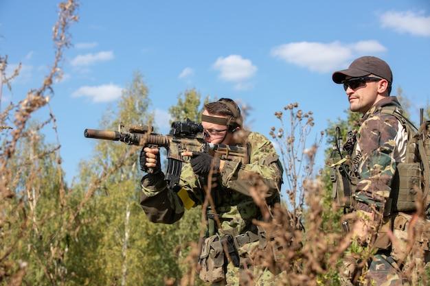 Gruppe von soldaten im freien auf armeeübungen. kriegs-, armee-, technologie- und menschenkonzept