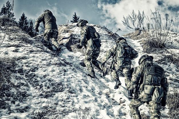 Gruppe von spezialeinheiten klettert in die berge, um eine günstige position zum schutz des ziels einzunehmen. gemischte medien