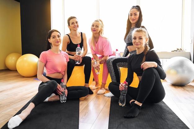 Gruppe von sportlichen frauen, die spaß an einer pause während des sporttrainings haben, trinken frisches wasser