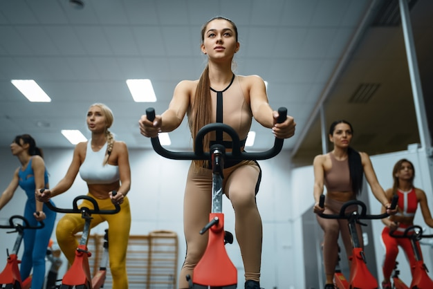 Gruppe von sportlichen frauen, die übung auf stationären fahrrädern im fitnessstudio, vorne tun